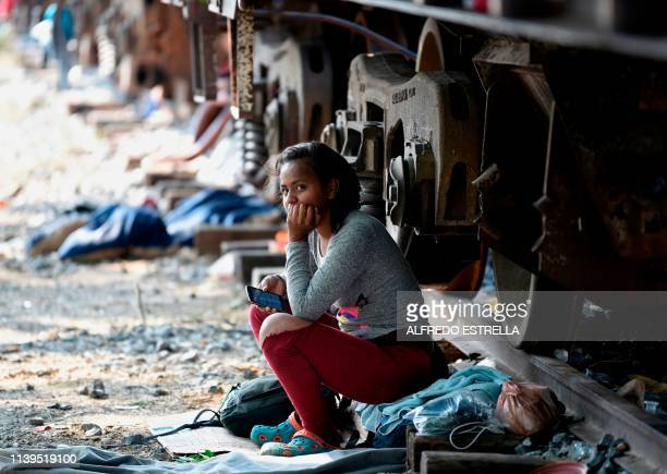 A Central American migrant rests by a train in Arriaga Chiapas Mexico on April 26 2019 Central American migrants at a detention center in southern...