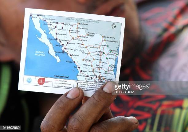 A Central American migrant shows a map of Mexico's train routes as he waits to board a train known as The Beast to reach the border with the US in...