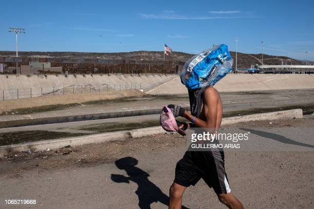 A Central American migrant takes a plastic bag over his head as he walks along the almost dry riverbed of the Tijuana River near the El Chaparral...