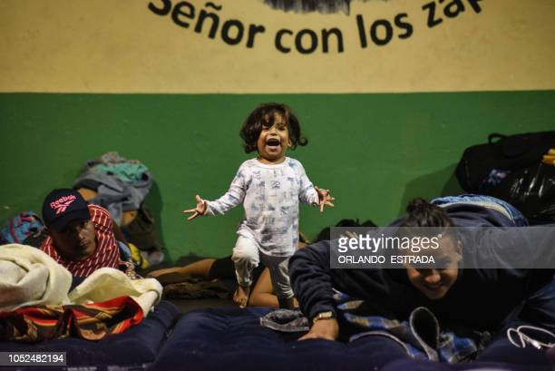 Central American migrant toddler heading in a caravan to the United States laughs as she rests with her family at the 'Casa del Migrante' in...
