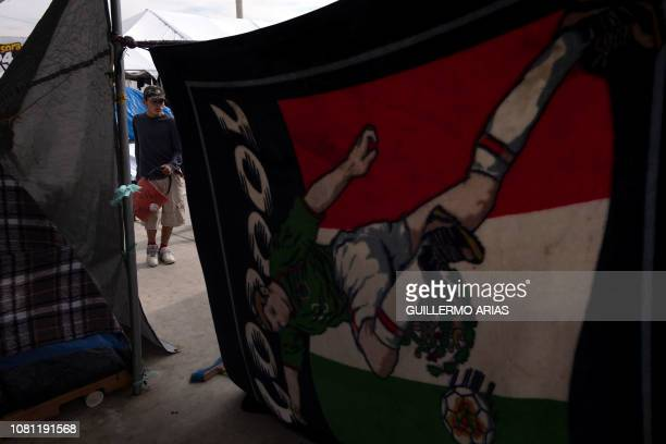 A Central American migrant traveling in a caravan to the United States carries a bucket in the El Barretal temporary shelter in Tijuana Baja...