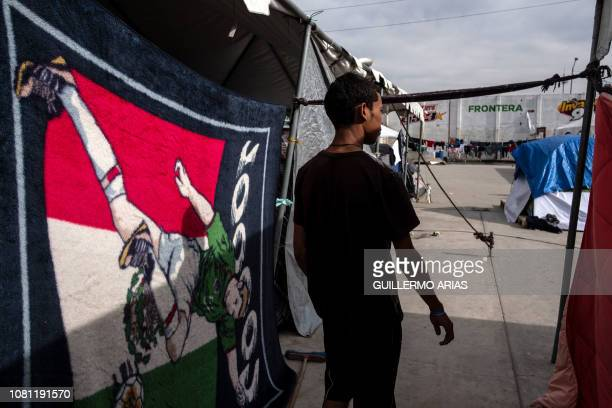A Central American migrant traveling in a caravan to the United States walks between tents at the El Barretal temporary shelter in Tijuana Baja...