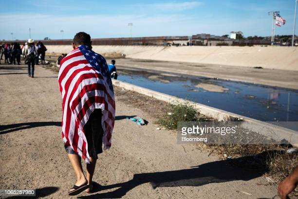 A Central American migrant wears an American flag near the US and Mexico border in Tijuana Mexico on Sunday Nov 25 2018 US border officials...