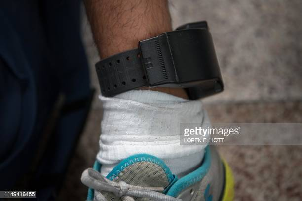 A Central American migrant wears an ankle monitor issued in federal detention after being released with fellow asylum seekers at a bus depot on June...
