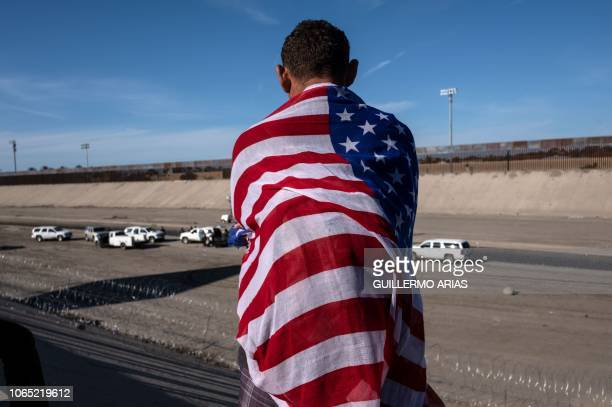 Central American migrant wrapped in a US flag looks at the almost dry riverbed of the Tijuana River near the El Chaparral border crossing near...