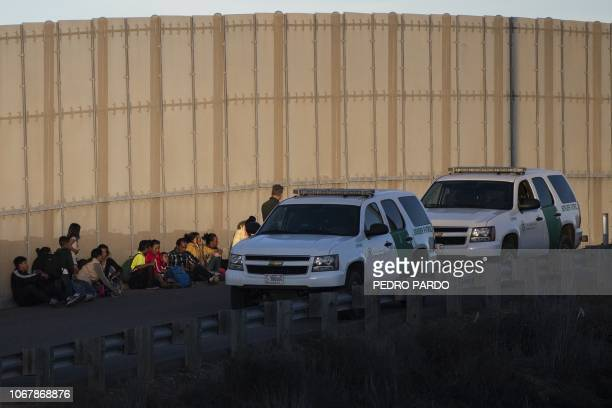 Central American migrants are arrested by US Border Patrol agents after jumping over the metal barrier separating Playas de Tijuana in Mexico from...
