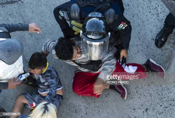 TOPSHOT Central American migrants are stopped by Mexican police forces as they reach the El Chaparral border crossing in Tijuana Baja California...