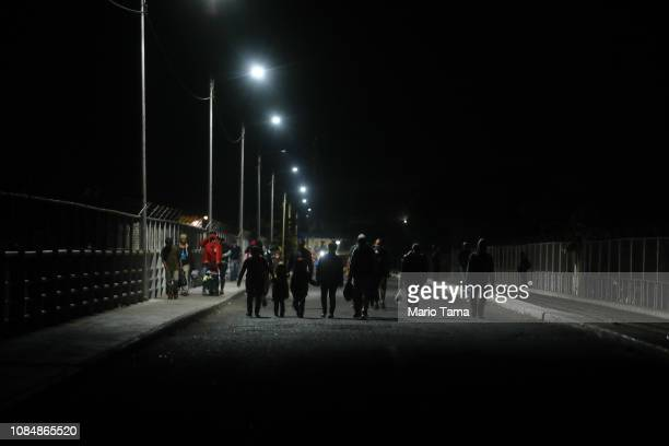 Central American migrants cross the international border bridge between Guatemala and Mexico without registering with authorities before dawn on...