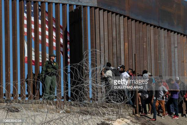 TOPSHOT Central American migrants look through a border fence as a US Border PatRol agents stands guard near the El Chaparral border crossing in...