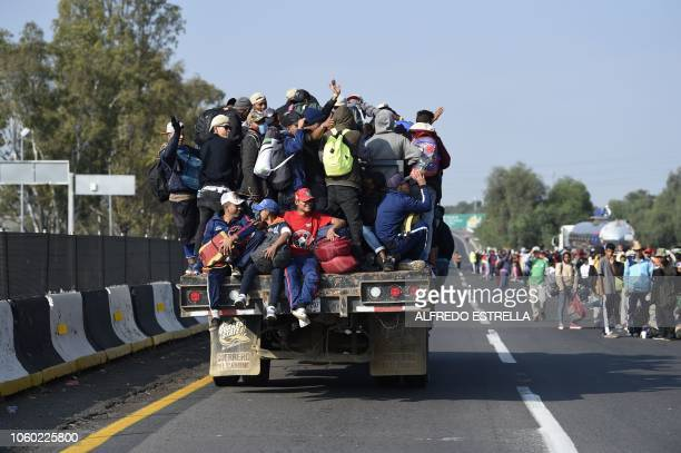 Central American migrants -mostly honduran- taking part in a caravan to the US, are pictured on board a truck heading to Irapuato in the state of...