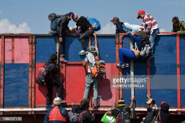 TOPSHOT Central American migrants mostly honduran taking part in a caravan to the US get on board a truck heading to Irapuato in the state of...
