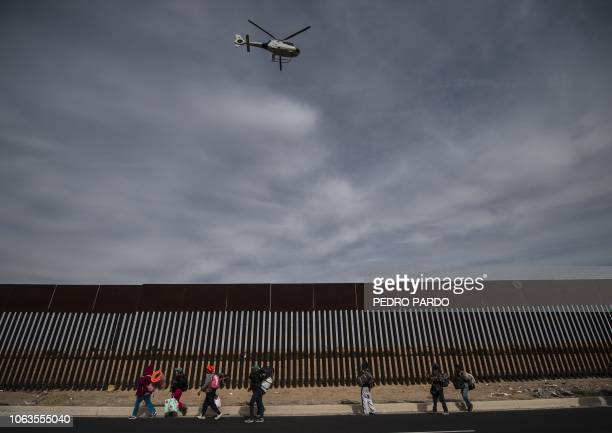 Central American migrants mostly Hondurans moving in a caravan towards the United States in hopes of a better life walk along the metal fence on the...