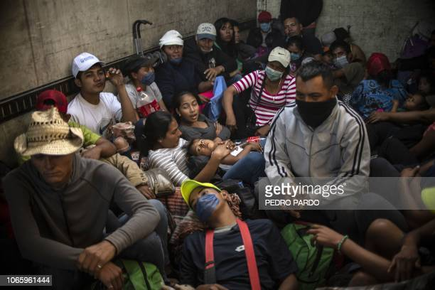 TOPSHOT Central American migrants mostly Hondurans moving in a caravan towards the United States in hopes of a better life travel in a truck from...