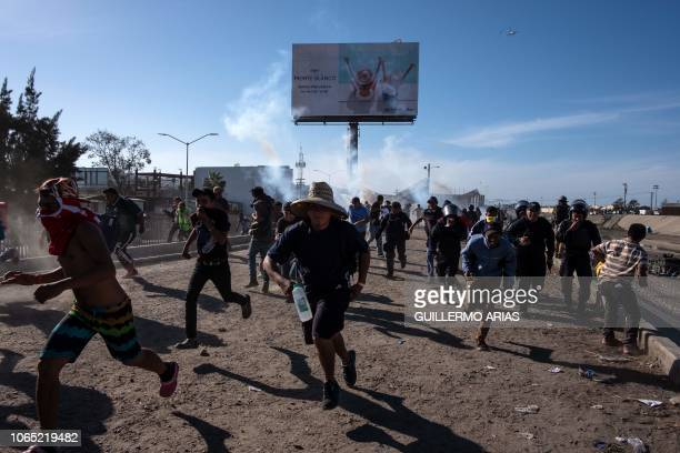 Central American migrants mostly Hondurans run along the Tijuana River near the El Chaparral border crossing in Tijuana Baja California State Mexico...