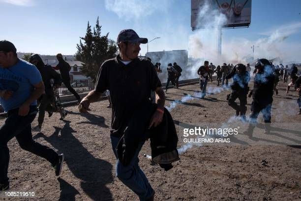 TOPSHOT Central American migrants mostly Hondurans run along the Tijuana River near the El Chaparral border crossing in Tijuana Baja California State...