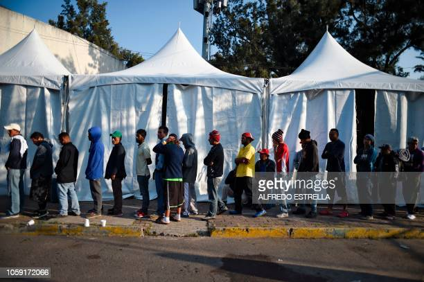 TOPSHOT Central American migrants mostly Hondurans taking part in a caravan towards the US queue for food at a shelter set up at the Sports City in...