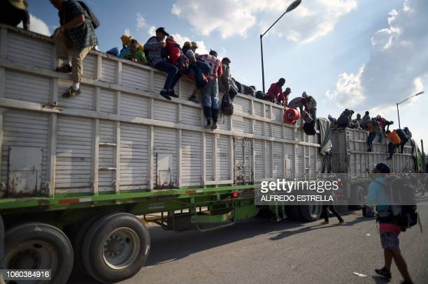 Central American migrants -mostly Hondurans- taking part in a caravan heading to the US, descend from a truck, on arrival at a temporary shelter in...