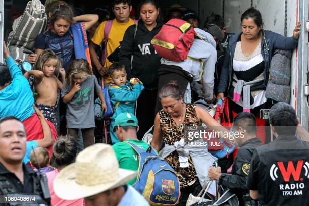 Central American migrants moving in a caravan towards the United States descend from a truck to be taken to a shelter in the outskirts of Zapotlanejo...