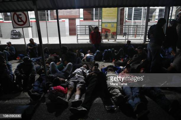 Central American migrants part of a new 'migrant caravan' rest and sleep after crossing a border bridge between Guatemala and Mexico to register at...