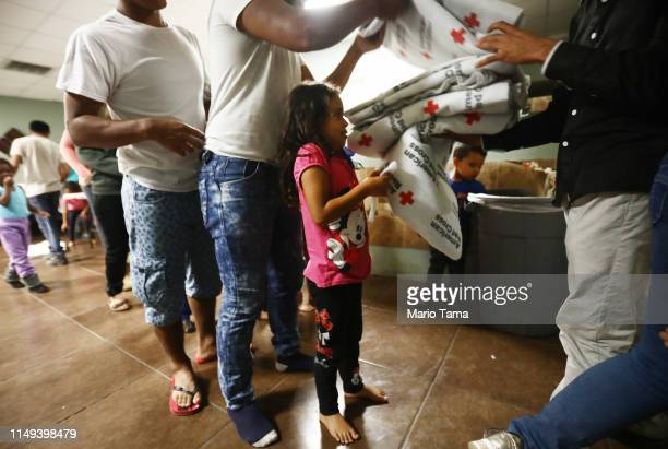 Central American migrants receive Red Cross blankets before sleeping on cots in a shelter for migrants on May 15 2019 in El Paso Texas Approximately...