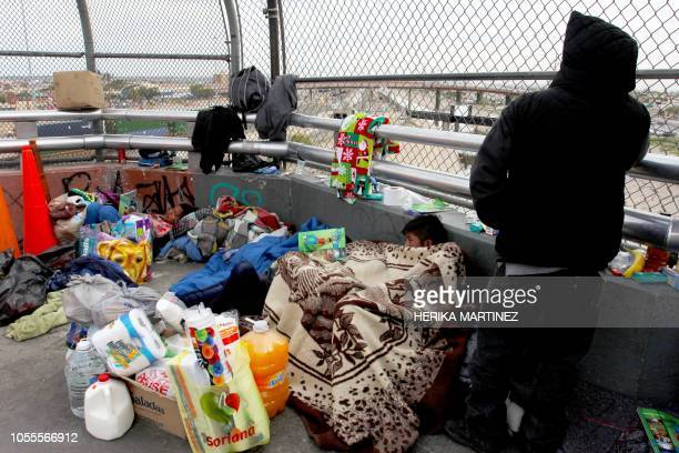 TOPSHOT Central American migrants rest at the Paso del Norte international bridge in Ciudad Juarez Mexico in the border with the US on October 30...