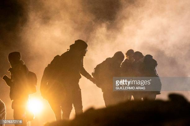 Central American migrants run away from tear gas thrown by the US border patrol after they tried to cross from Tijuana to San Diego in the US as seen...