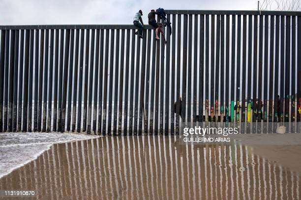 Central American migrants sit above the USMexico border fence as a Border Patrol agent stands guard as seen from Tijuana to San Diego as seen from...