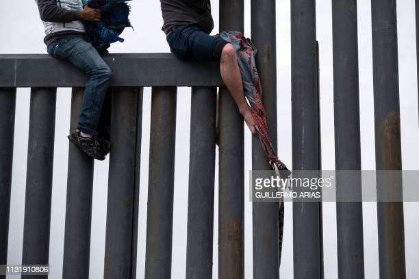 Central American migrants sit above the USMexico border fence while trying to make a rope to help others to cross as seen from Playas de Tijuana in...