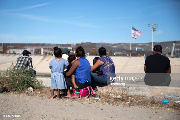 Central American migrants sit along the Tijuana River as an American flag flies near the US and Mexico border in Tijuana Mexico on Sunday Nov 25 2018...