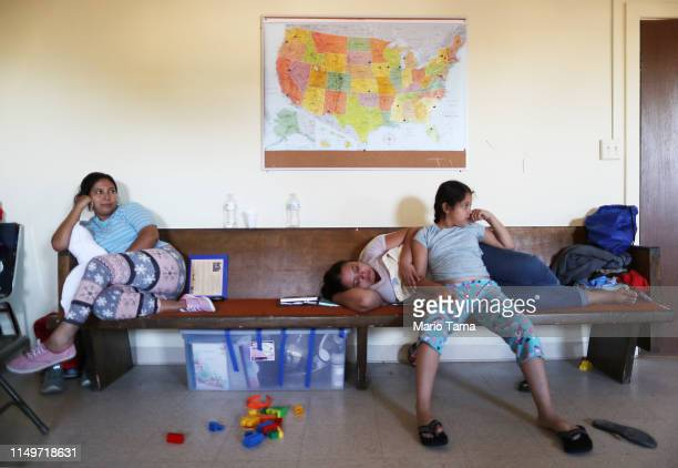 Central American migrants sit beneath a map of the US in a shelter for migrants who are seeking asylum on May 16 2019 in Las Cruces New Mexico After...