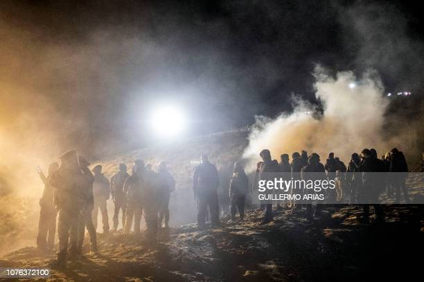 Central American migrants stand amid a cloud of tear gas thrown by the US border patrol after they tried to cross from Tijuana to San Diego in the US...