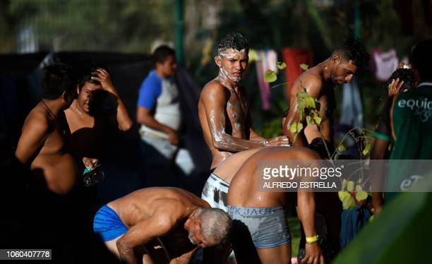Central American migrants, taking part in a caravan heading to the US, wash themselves at a temporary shelter in Irapuato, Guanajuato state, Mexico...