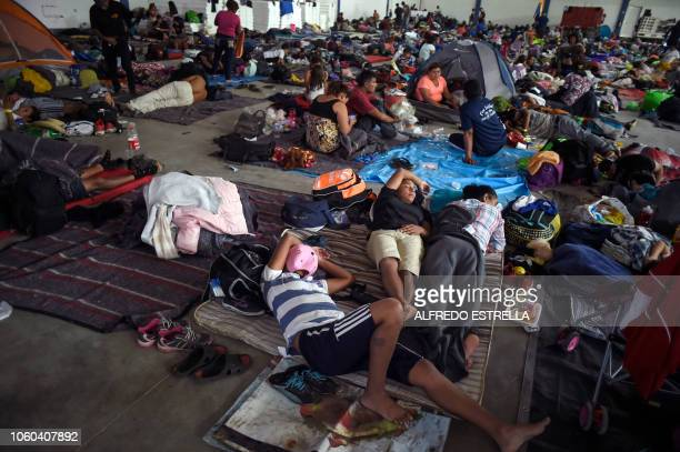 Central American migrants taking part in a caravan heading to the US rest at a temporary shelter in Irapuato Guanajuato state Mexico on November 11...