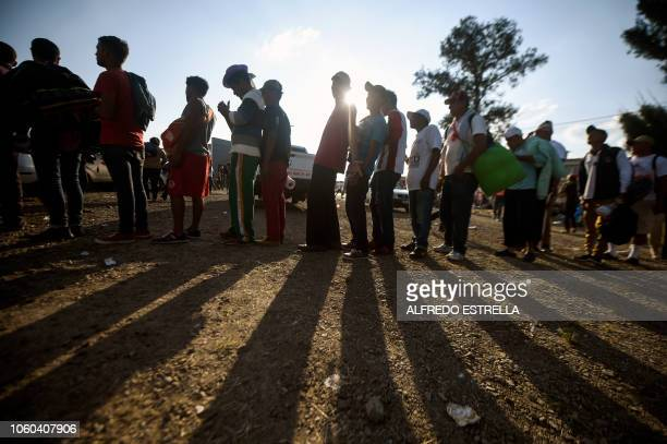 Central American migrants taking part in a caravan heading to the US queue to receive a meal at a temporary shelter in Irapuato Guanajuato state...