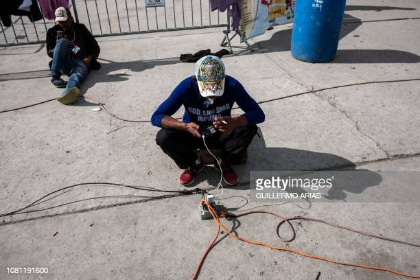 Central American migrants traveling in a caravan to the United States use their cellphones at the El Barretal temporary shelter in Tijuana Baja...