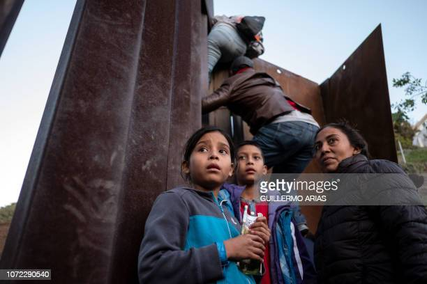 TOPSHOT Central American migrants travelling in a caravan hesitate as others climb the MexicoUS border fence in an attempt to cross to San Diego...