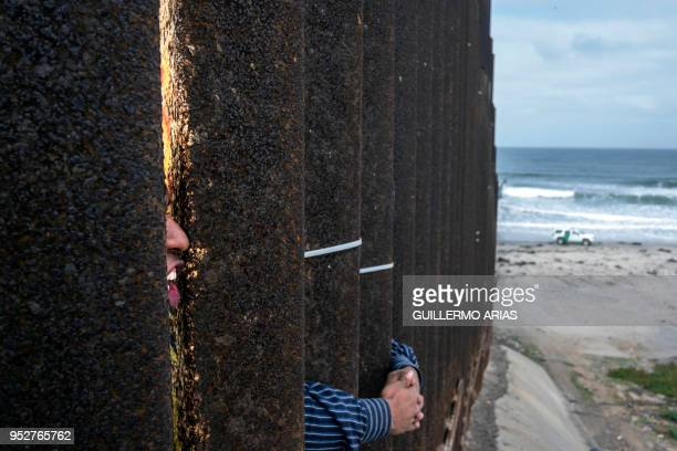 TOPSHOT Central American migrants travelling in the Migrant Via Crucis caravan demonstrate at the US/Mexico Border at Tijuana's beaches Baja...