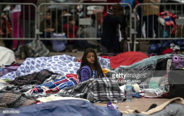 Central American migrants travelling in the Migrant Via Crucis caravan sleep outside El Chaparral port of entry to US while waiting to be received by...