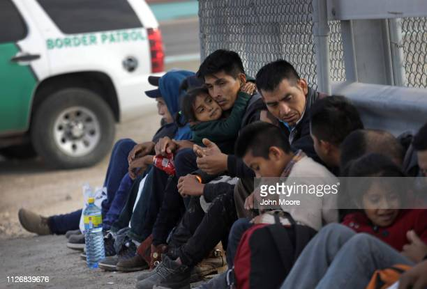 Central American migrants wait to be taken into custody after crossing into the United States from Mexico on February 01 2019 in El Paso Texas The...