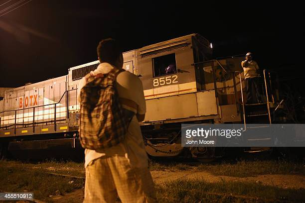 Central American watches as a freight train arrives on September 15 2014 in Tenosique Mexico Many migrants have perished riding atop La Bestia or The...