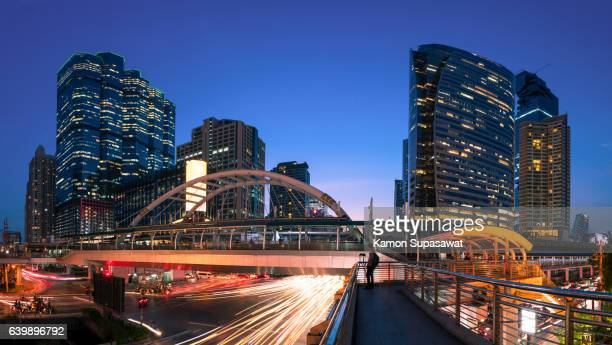 Central Bangkok cityscape in twilight with long light trail on street