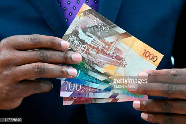 Central Bank of Kenya Governor Patrick Njoroge displays some of the new look shilling Kenyan currency notes on June 3 2019 during a press conference...