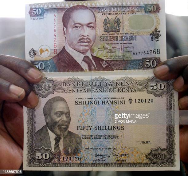 A Central bank of Kenya official displays notes bearing the portrait of founding president Jomo Kenyatta that were withdrawn after his death but will...