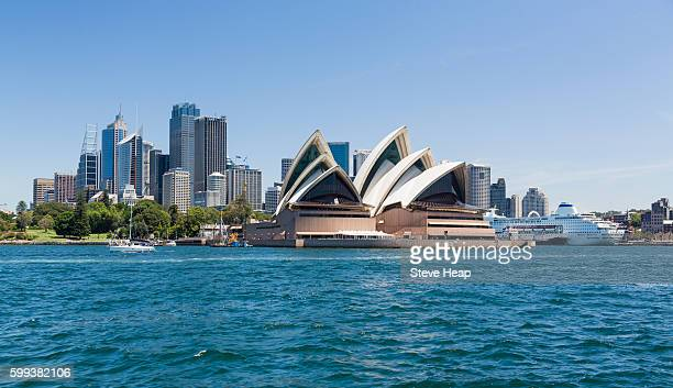 central business district of sydney and the opera house with p&o pacific pearl cruise ship docked in the harbor, australia - sydney pearl stock-fotos und bilder