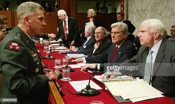 S Central Command Commander Gen John Abizaid talks to Sen John McCain Chairman Sen John Warner and Sen Carl Levin prior to a hearing before the...