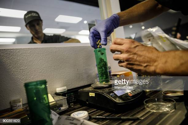 Central employee Kevin Gardner right Dispenses a customer's order at 420 Central in Santa Ana Calif on Jan 1 2018 The state has issued dozens of...