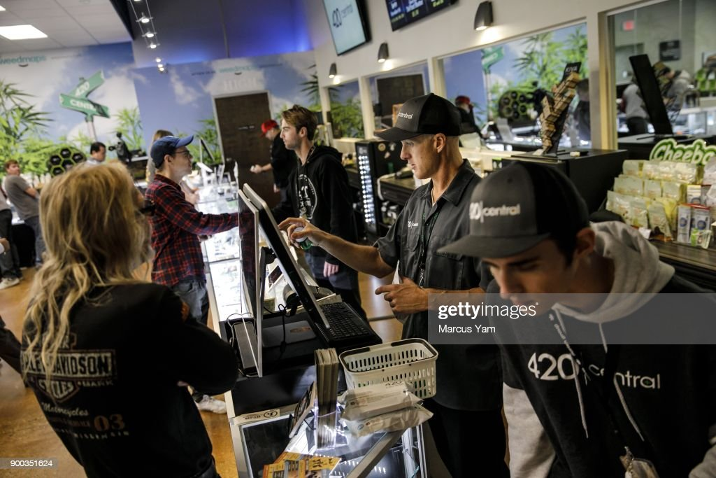 Central employee Kevin Gardner, second from right, rings up a customer's order at 420 Central, in Santa Ana, Calif., on Jan. 1, 2018. The state has issued dozens of permits for retailers to begin recreational sales this week, expanding a market that is expected to grow to $7 billion annually by 2020. Several of those retailers are in West Hollywood, but they won't open until Tuesday at the city's request. That makes Santa Ana's licensed stores the closest option for Angelenos who want to buy recreational marijuana on New Year's Day. Buyers could also trek to San Diego or the Palm Springs area to purchase pot.