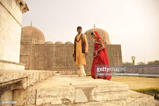 central group. two people with traditional indian clothing near hoshang shah's tomb - hoshang shah's tomb stock pictures, royalty-free photos & images