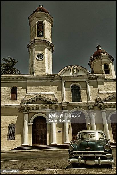 Central Havana, Cuba, vintage car parking along buildings in front of a church