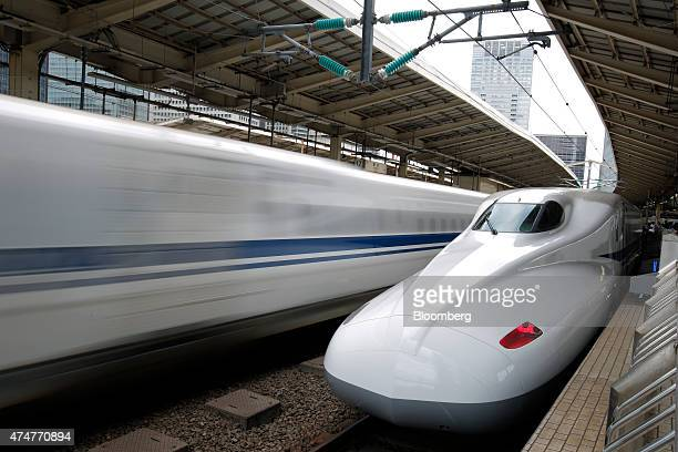 A Central Japan Railway Co N700 series Shinkansen bullet train right stands on the platform while another departs from Tokyo Station in Tokyo Japan...